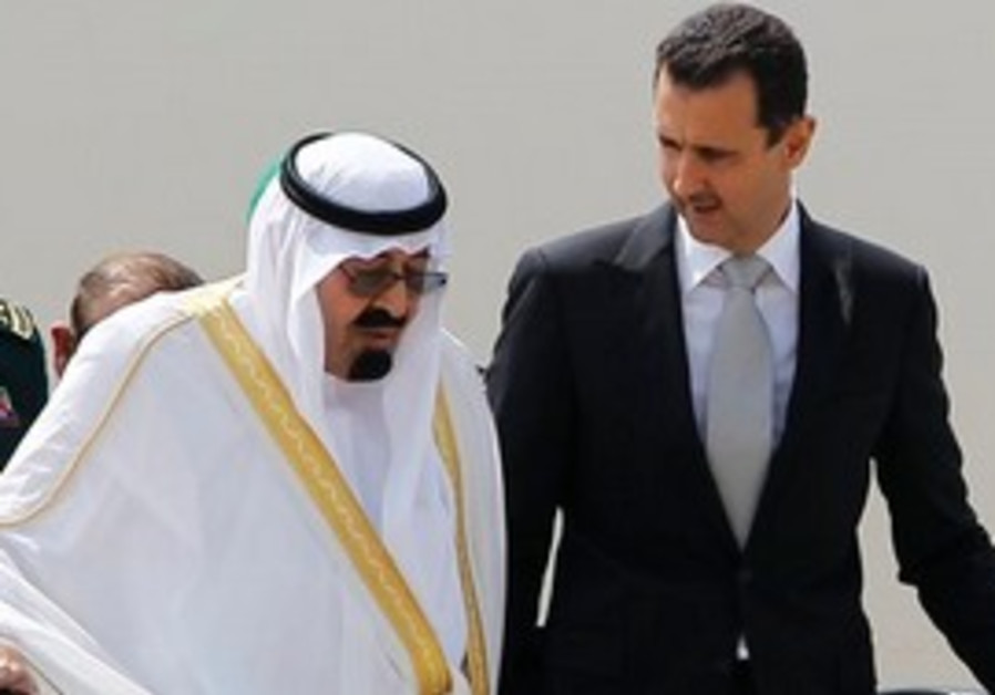 Saudi King Abdullah, left, and Syrian President Bashar Assad, right, talk to each other as they step