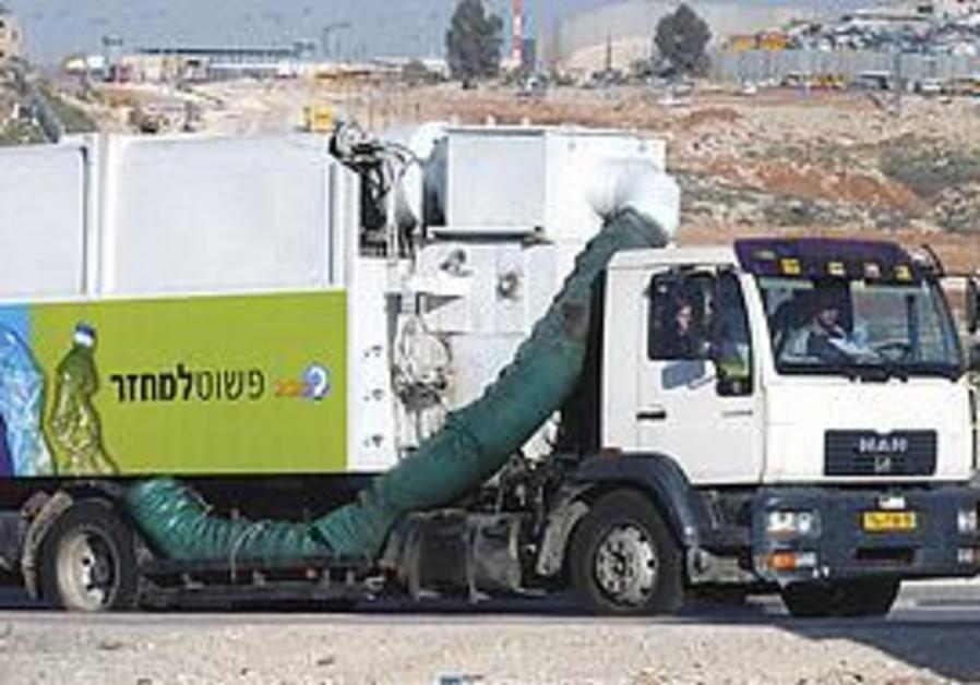 A RECYCLING truck is seen en route to discharging its cargo of plastic bottles.