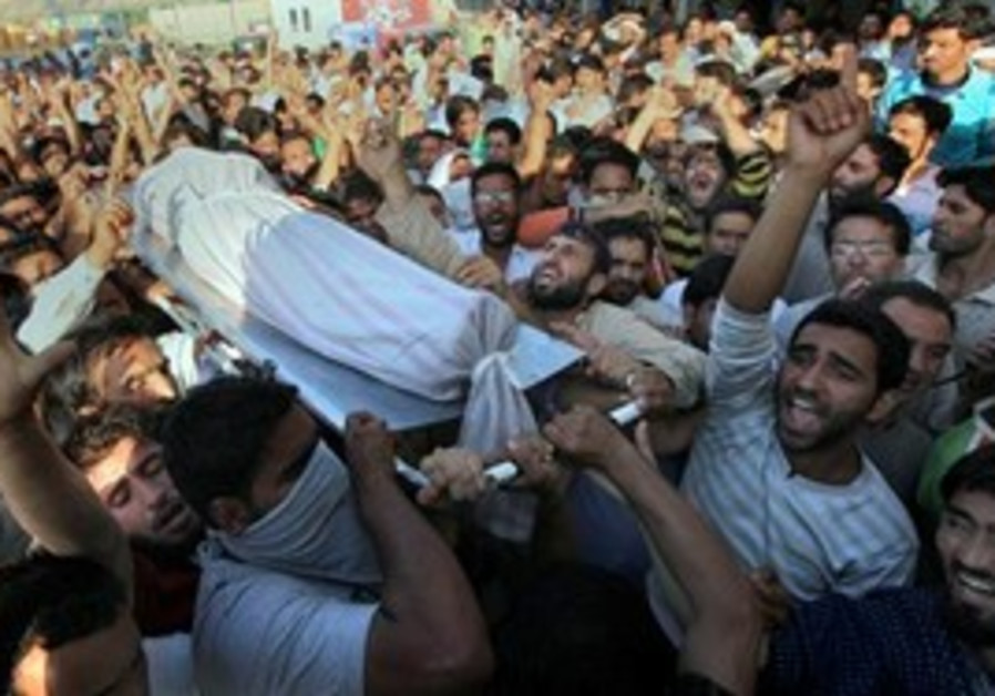 Kashmiri men shout pro freedom slogans as relatives and friends carry the dead body of Afroza Wani o
