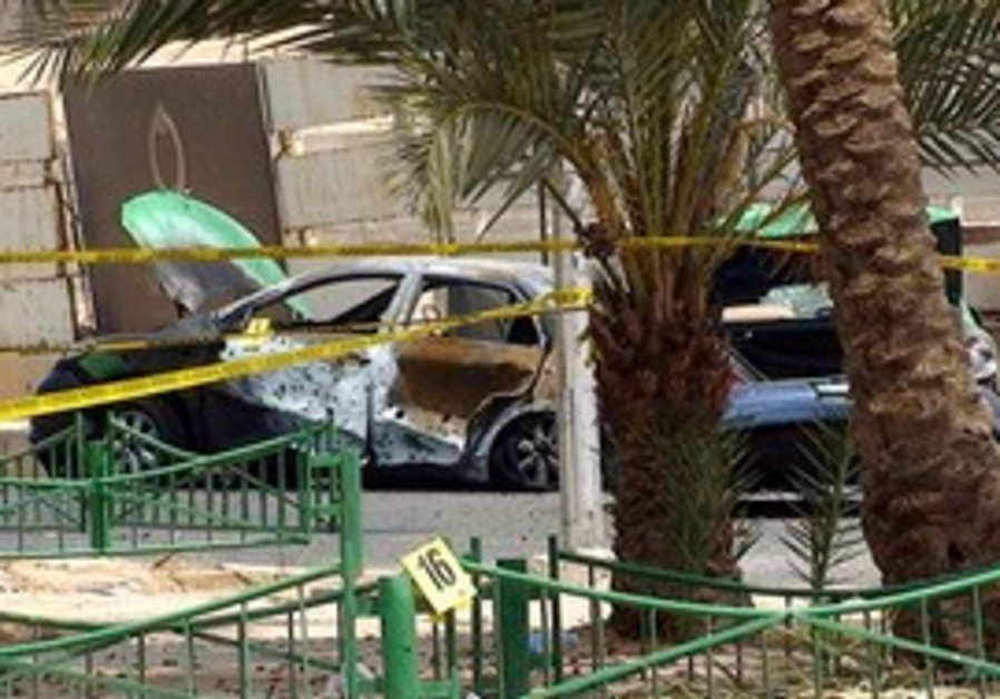 A damaged car is seen at the site of a rocket attack, in front of the Intercontinental Hotel in the