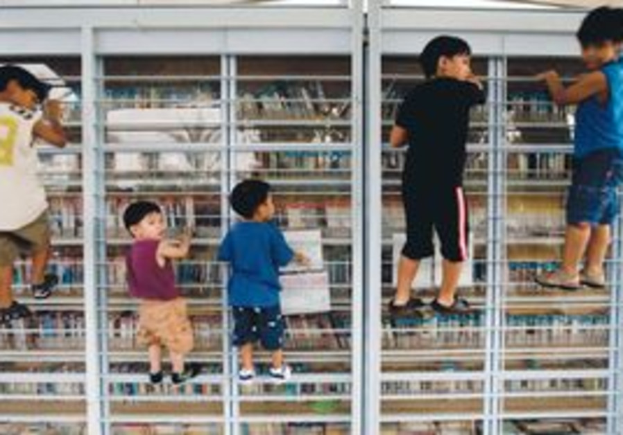 Children of foreign workers climb a metal bookcase in Tel Aviv as their parents meet .