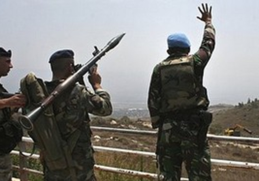 A UNIFIL peacekeeper, right, waves as a Lebanese soldier, center, carries an RPG in front of IDF tro