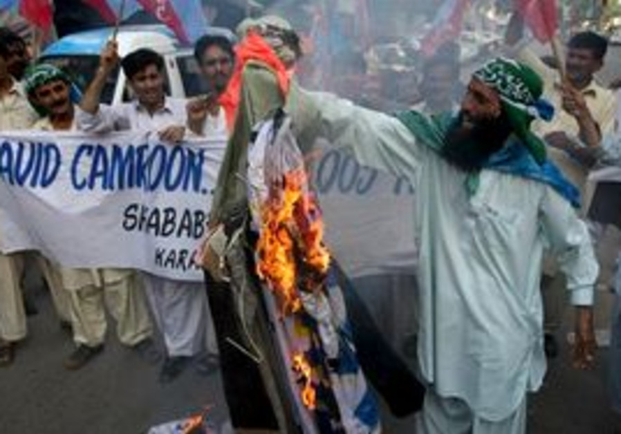Pakistanis burn an effigy of British PM David Cameron after he suggested that Pakistan exports Islam