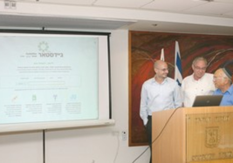 JUSTICE MINISTER Yaakov Neeman (right) launches the GuideStar Web site at a Jerusalem press conferen