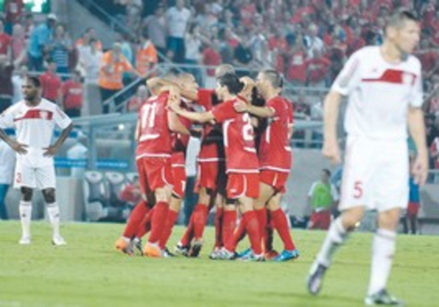 HAPOEL TEL AVIV players embrace after taking a 3-0 first-half lead at Bloomfield Stadium last night