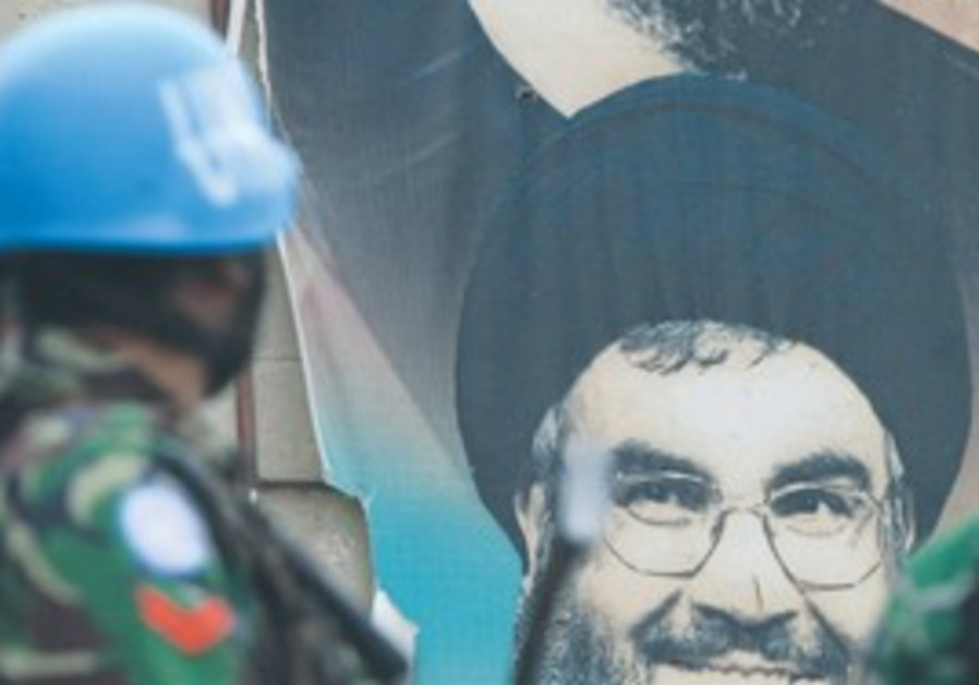 INDONESIAN U.N. peacekeepers patrol the area near a poster of Hizbullah leader Hassan Nasrallah, in