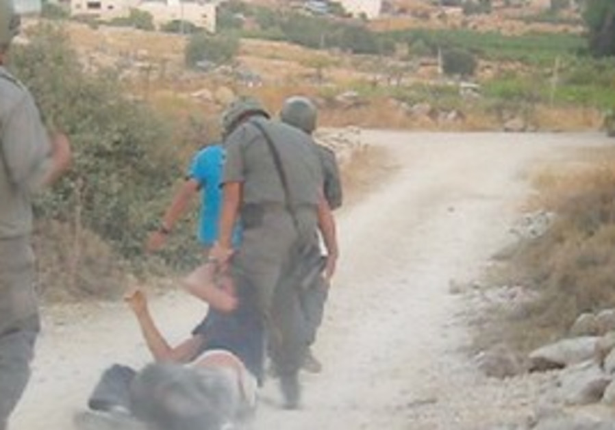 A BORDER policeman drags a settler youth along the ground by his sidelocks yesterday during the demo