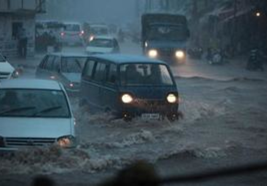 Vehicles move through a flooded road during heavy rains in Jammu, India, Sunday, Aug. 8, 2010. Monso