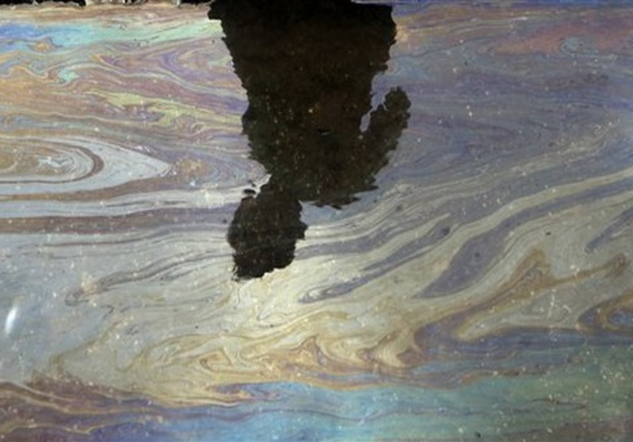A boy casts a shadow on the water contaminated with oil near the Arabian Sea shore in Mumbai, India,