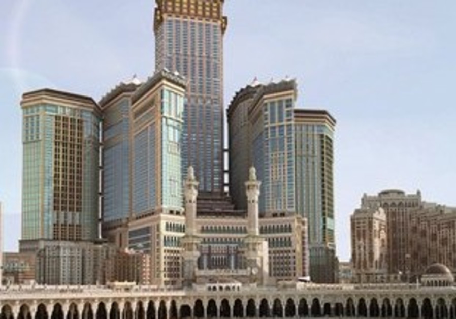 The four-faced clock, atop the Abraj Al-Bait Towers, at centre rear, in Mecca, Saudi Arabia stands o
