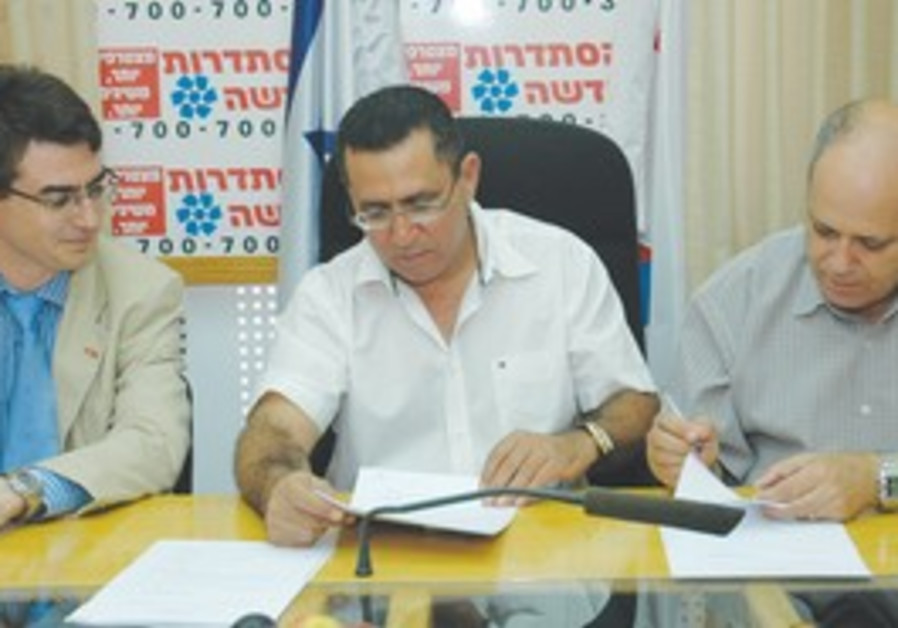 HISTADRUT CHAIRMAN Ofer Eini (middle) and representatives of the catering industry sign a collective