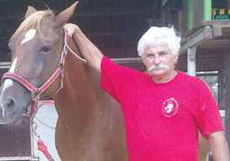 SHLOMO YA'ACOBI leads a friendly (non-biting) horse in Moshav Kfar Warburg, before his injury.