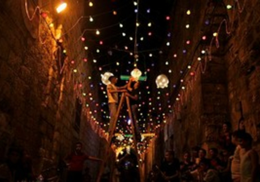 Palestinian Muslims decorate an alley of Jerusalem's old city with festive lights in preparation for