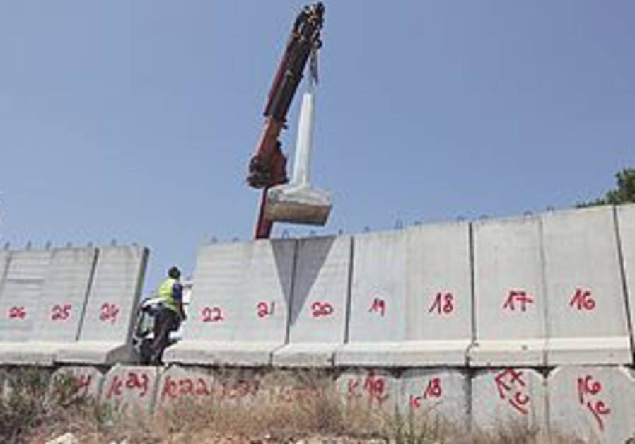 THE IDF starts removing sections of the protective barrier yesterday in Gilo after first numbering t
