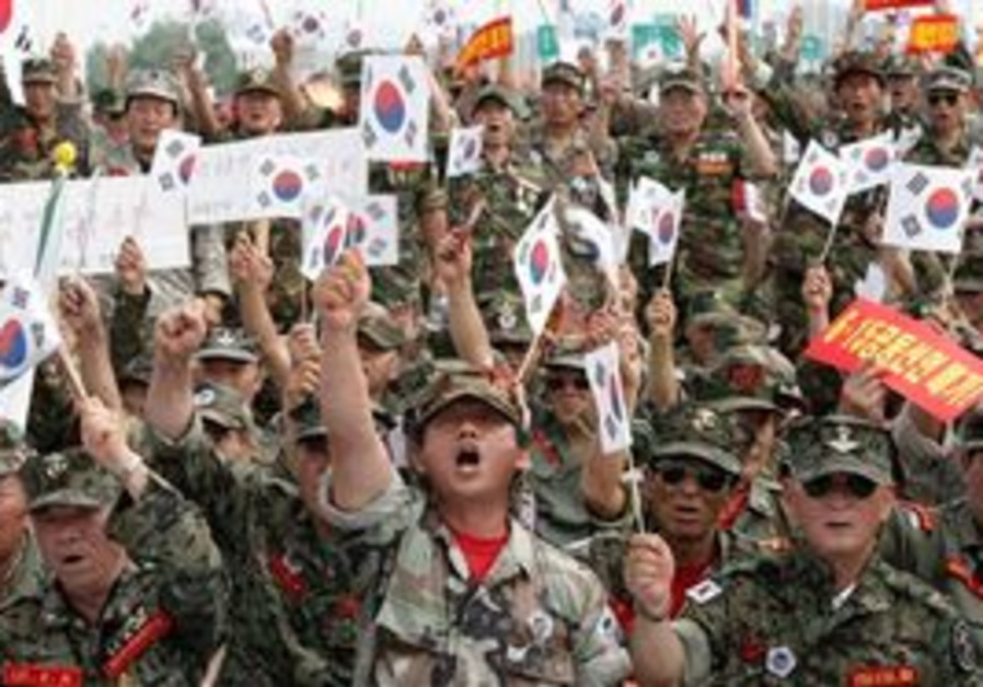 South Korean Vietnam War veterans with the national flags shout slogans during a rally against North