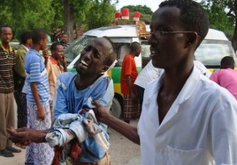 A wounded Somali man is assisted after being wounded in fighting.