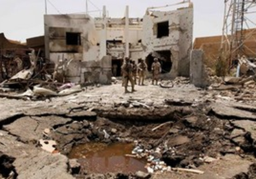 Iraqi army soldiers stand near a massive crater outside the office of the Al-Arabiya television stat