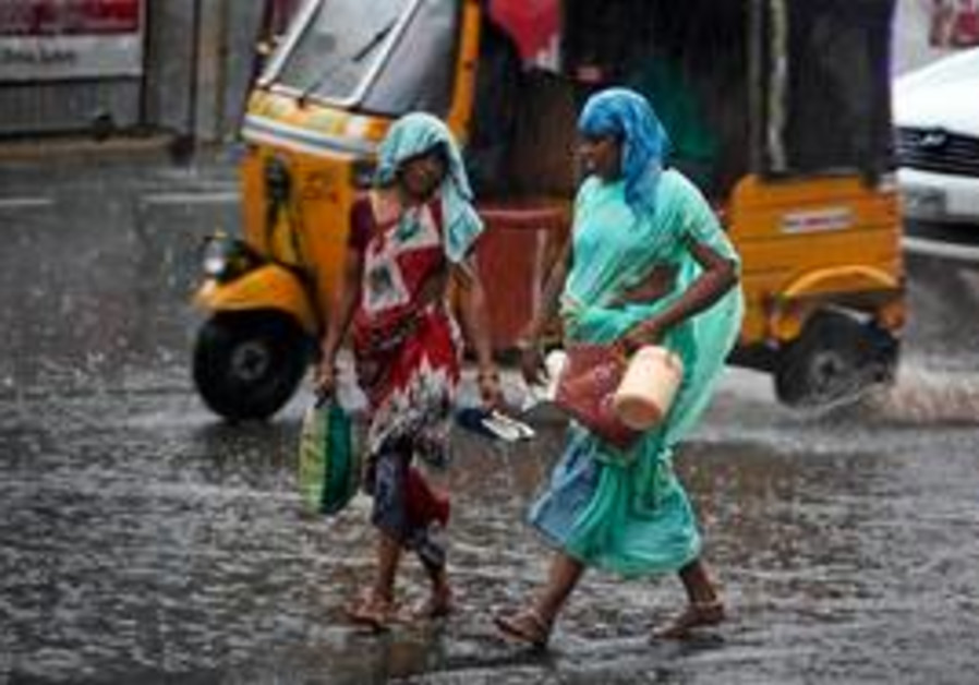 Two Indian women hold their sandals in hands as they walk in the rain in Hyderabad, India, Tuesday,