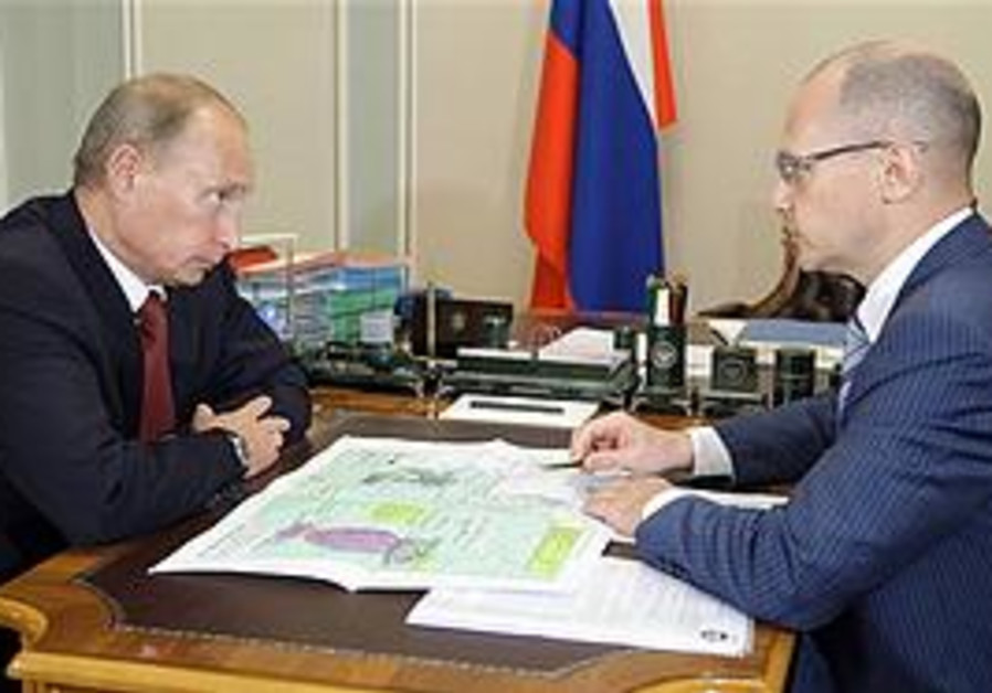Russian Prime Minister Vladimir Putin listens to the chief of the country's nuclear energy agency, R