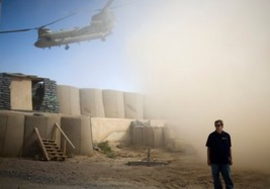 In this July 19, 2010 file photo, A U.S. contractor  looks away from a dust cloud whipped up by a h