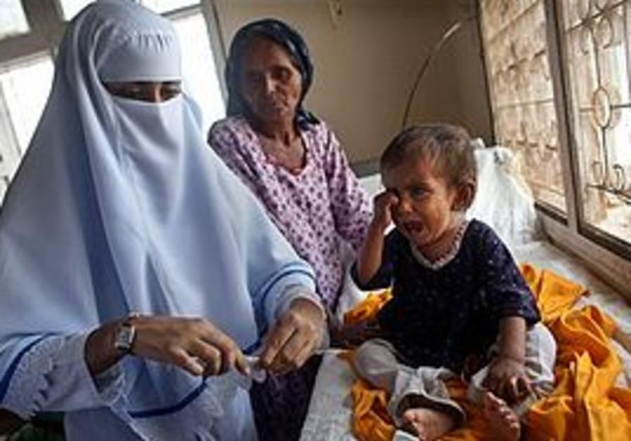 A nurse prepares to give antibiotic shots to a young Pakistani flood victim.