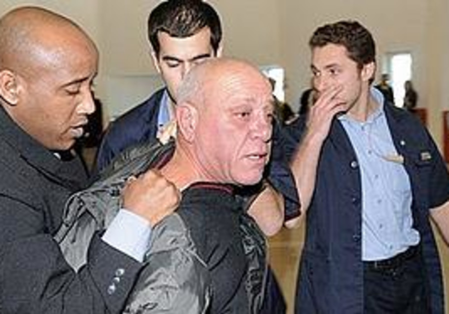 Pinchas Cohen, center, is detained by Supreme Court security guards after hurling his shoes at Israe