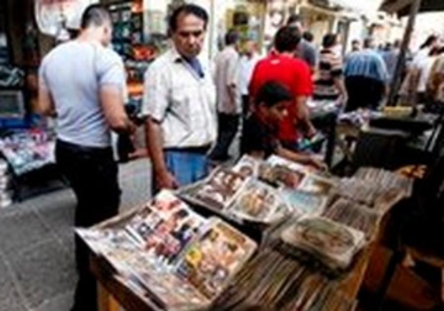 Iraqis walk by street vendor selling pornography