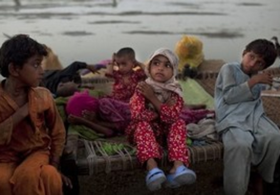 Pakistani children who were forced to flee flooding from their village sit on a bed on the roadside