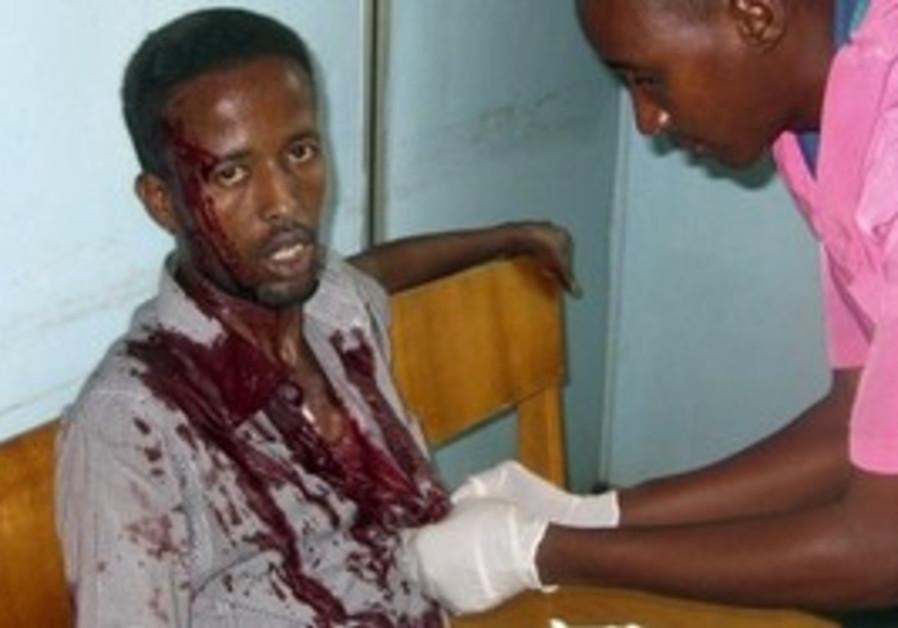 A nurse at Medina hospital treats a wounded civilian in Mogadishu, Somalia, Tuesday, Aug. 24, 2010.