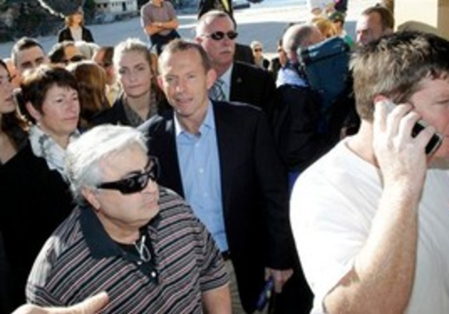Australia's  opposition leader Tony Abbott, center, lines up with voters at Queenscliff Beach pollin