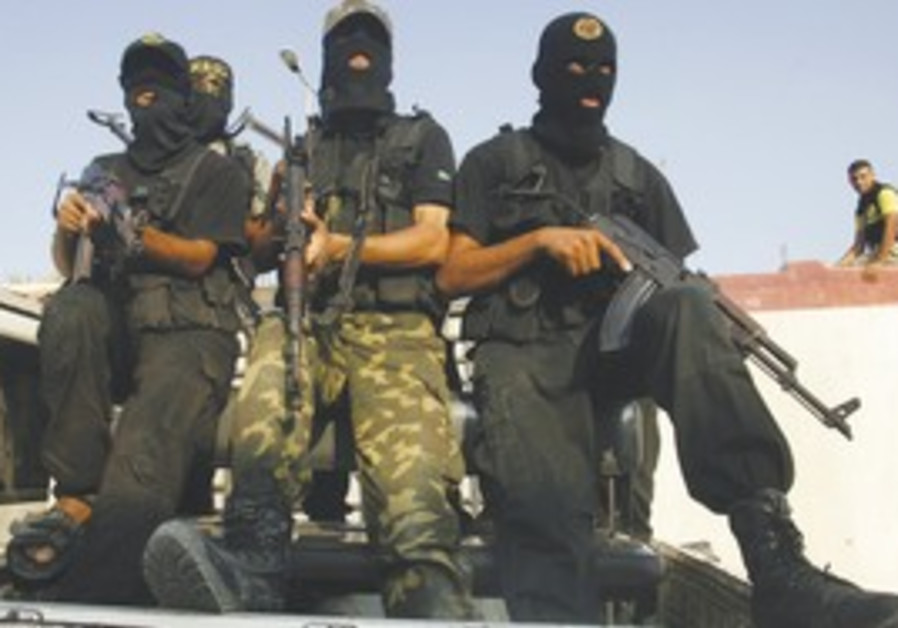 PALESTINIAN ISLAMIC JIHAD militants participate in the funeral of one of their comrades killed in fi