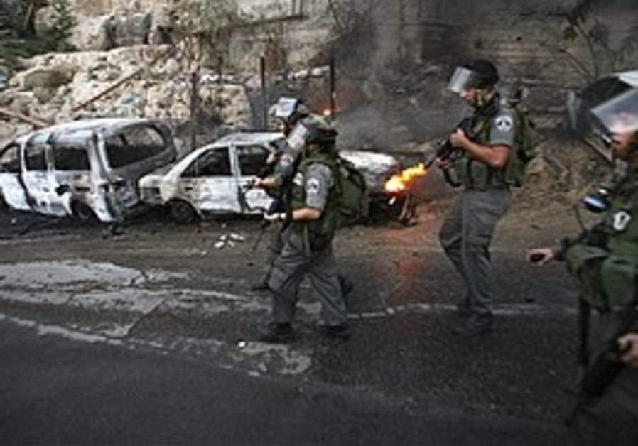 Border policemen walk next to burned cars in Silwan, Thursday