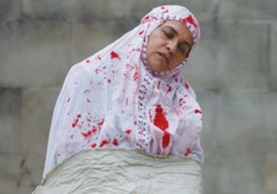 A PROTESTER, dressed to depict a woman being stoned to death in Iran, takes part in a demonstration