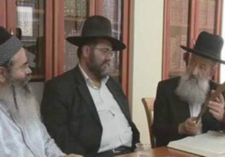 RABBI AMNON YITZHAk (left) listens to Rabbi Ben Zion Mutsafi as he speaks of the leather strip with