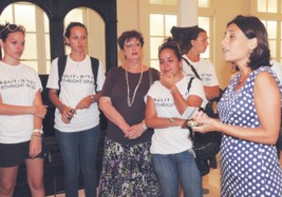 SURINAMESE BIRTHRIGHT participants and Surinamese olah Hannah Lindwer listen to curator Tania Coen-U