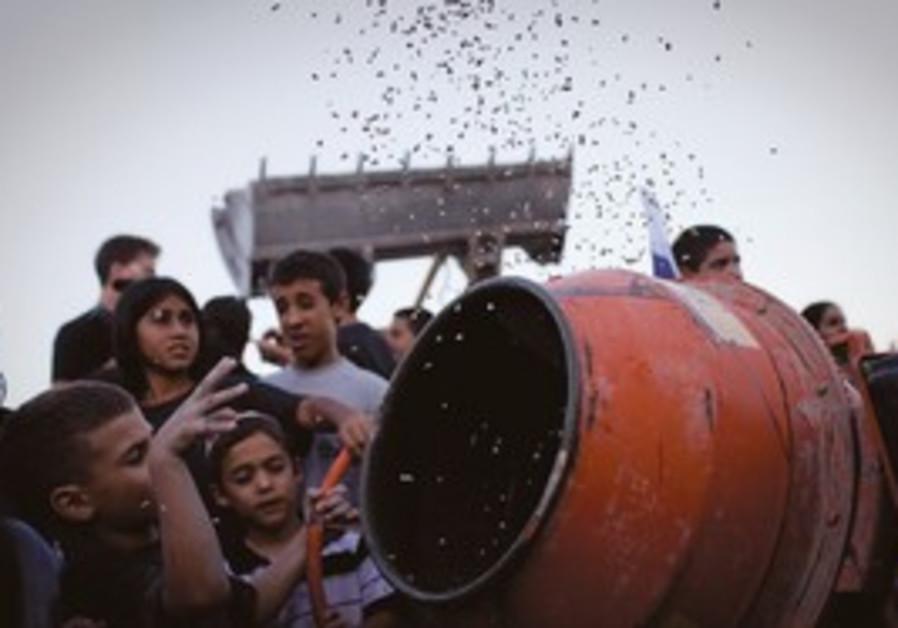 Children throw pebbles into cement mixer in Adam.