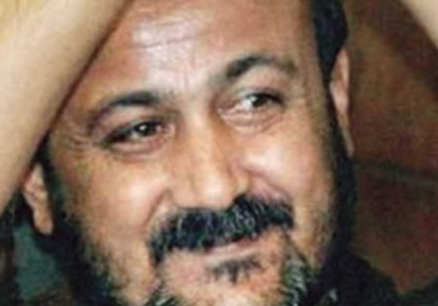 MARWAN BARGHOUTI smiles and raises his cuffed hand