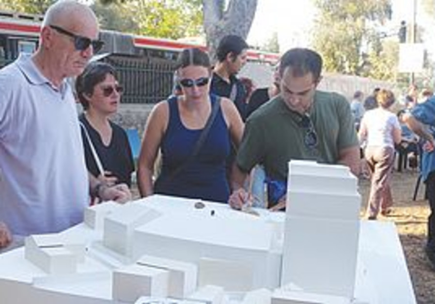 RESIDENTS LOOK at a model of the proposed hotel