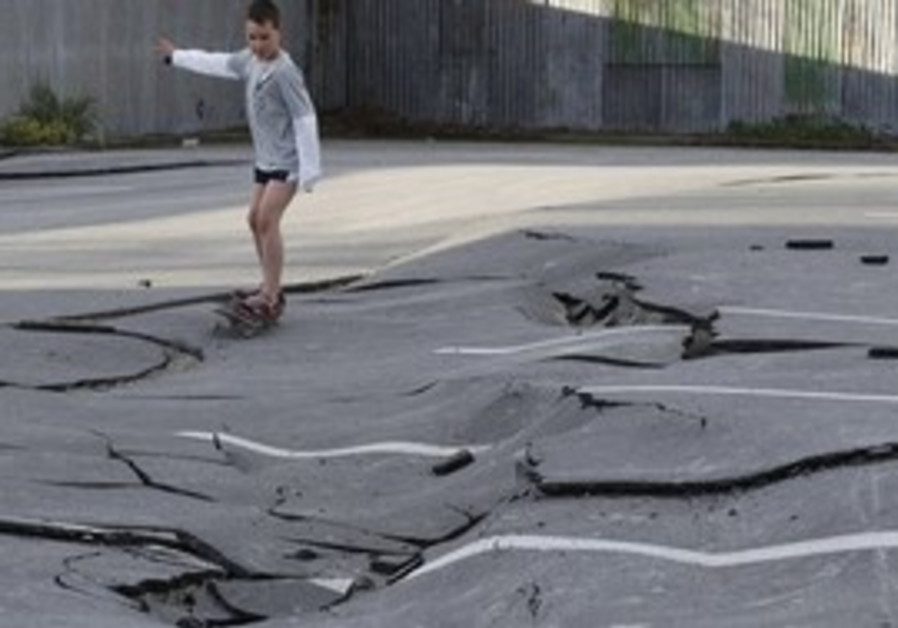 Boy skateboards on road shattered by 7.1 quake.