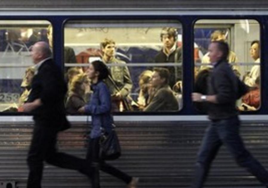 Commuters run to catch a train in the Paris Metro.