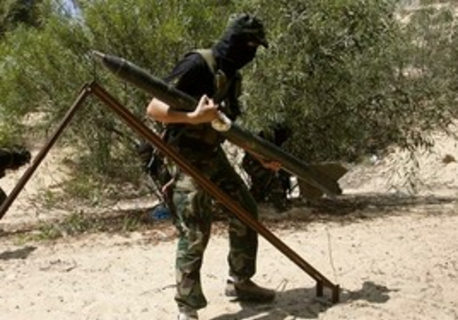 A Palestinian Islamic Jihad militant holds a rocke