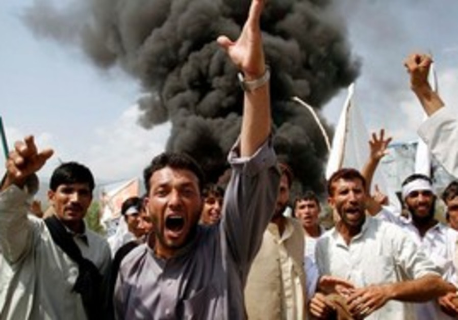 Afghans shout anti-U.S. slogans as they burn tires