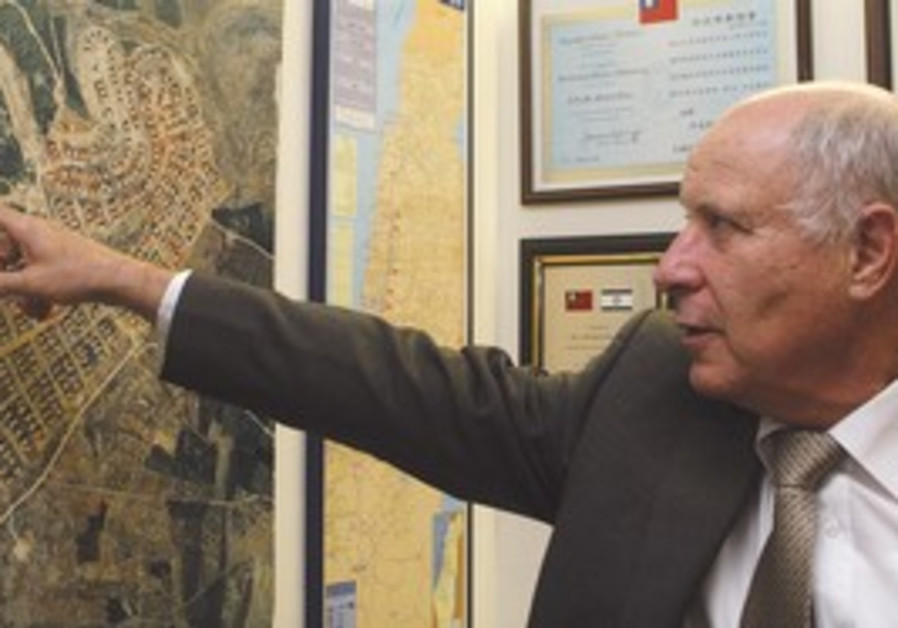 Michael Eitan pointing to a settlement map.