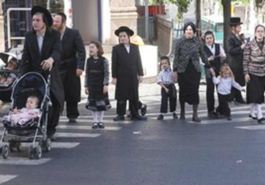 HAREDI MEN and women cross the street yesterday in