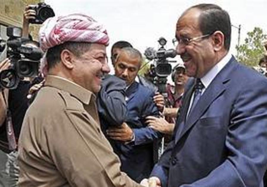Maliki shakes hands with Kurdish leader.