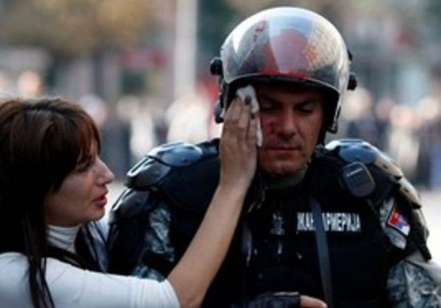 A member of the Serbian riot police is assisted