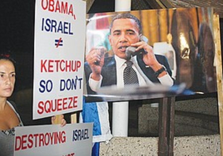 A protester next to a poster of US President Obama