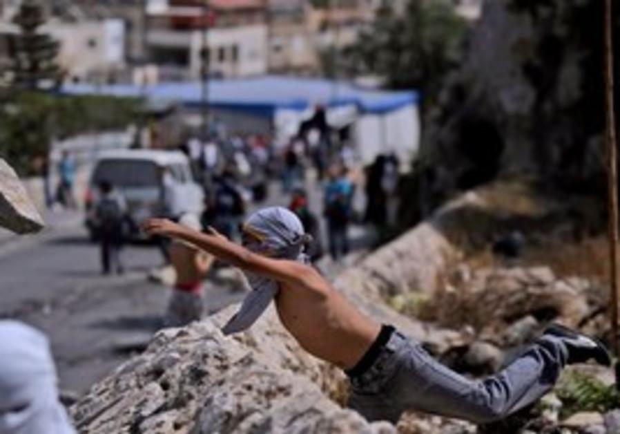 Masked youth throwing rocks in Silwan