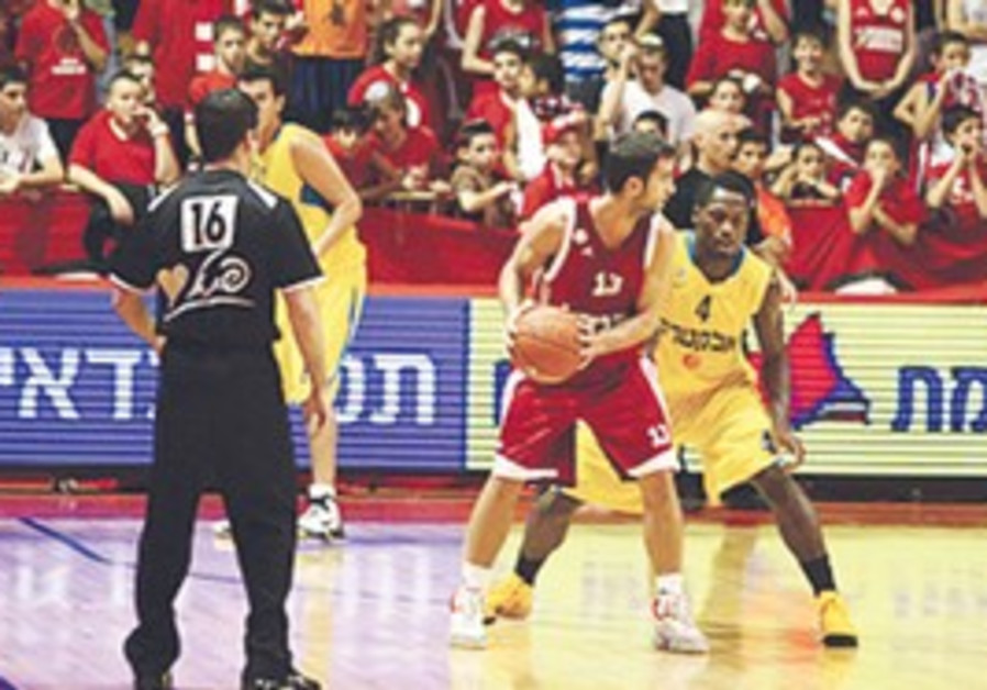 HAPOEL JERUSALEM guard Yogev Ohayon (with ball) ha