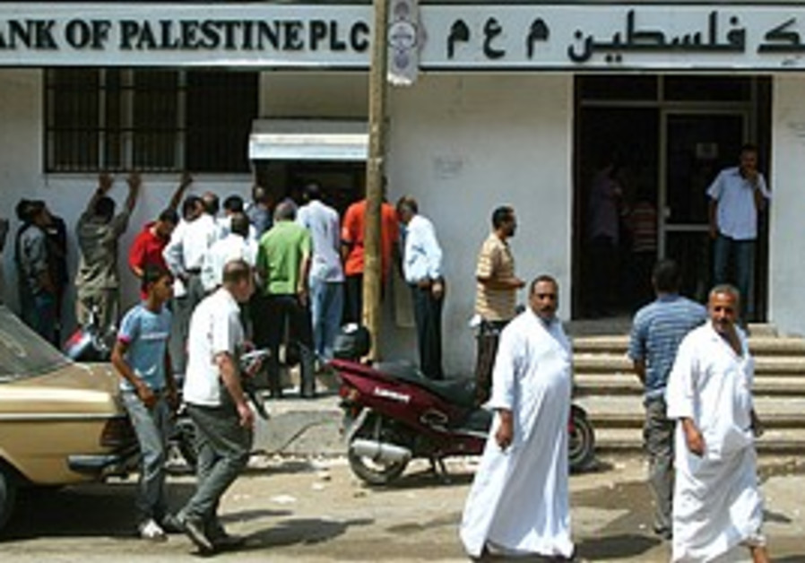 Gazans wait to draw money from an ATM in Rafah